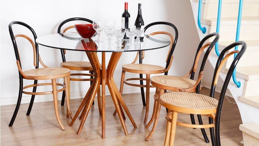 Mesa de vidro redonda com cadeiras de madeira e palha, taças e garrafas de vinho | Westwing.com.br