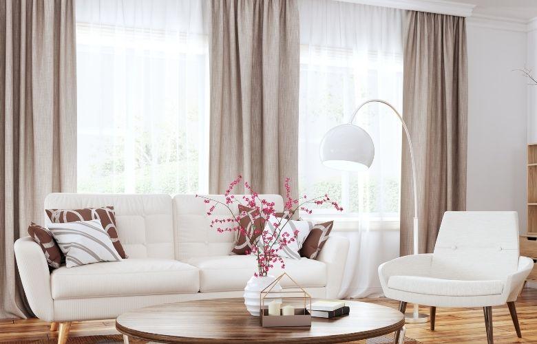 sala-de-estar-com-um-sofa-e-uma-cadeira-e-cortina-branca