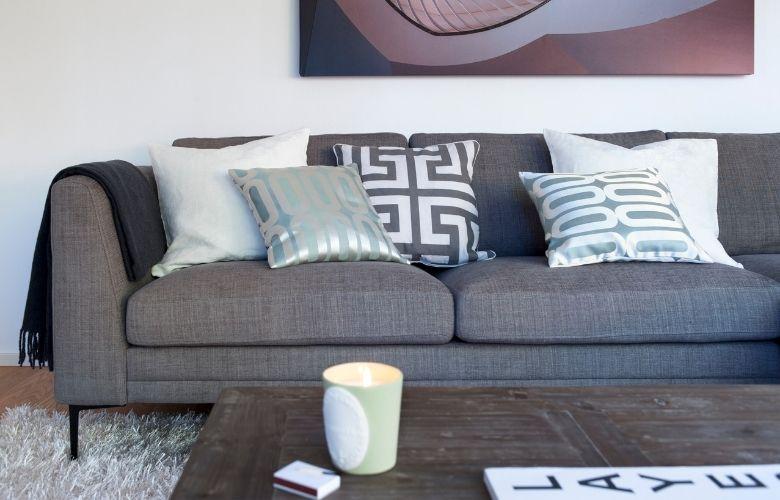 sofá cinza com almofadas cinza de estampas geoétricas