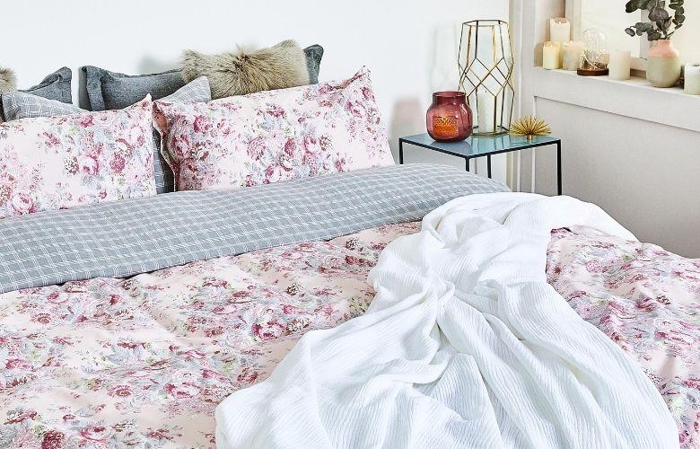 detalhe de cama floral com xadrez e mesa de apoio com decorativos ao lado
