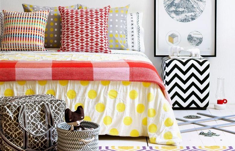 cama com lençois manta e almofadas de estampas