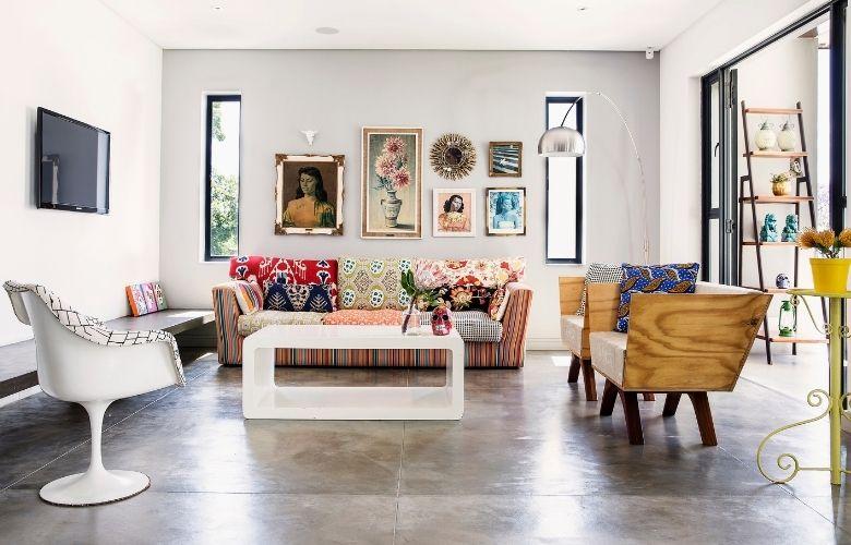 sala ampla com sofa de estofado com poltronas e almofadas coloridas