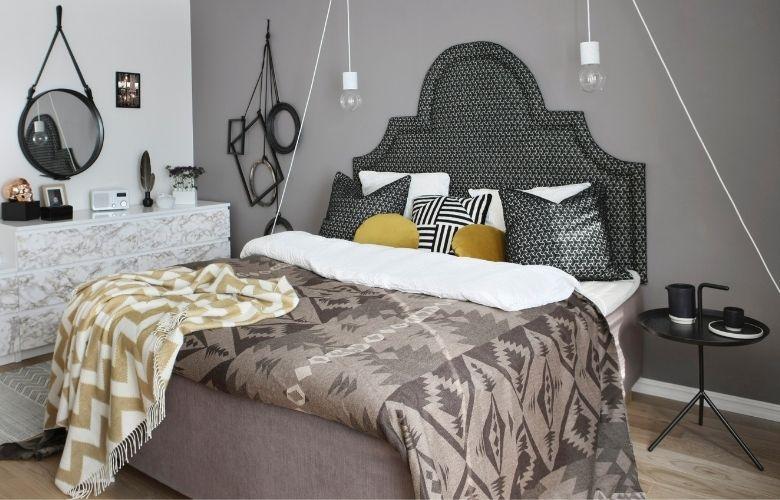 quarto com cama de casal em tons de cinza e edredom e almofadas