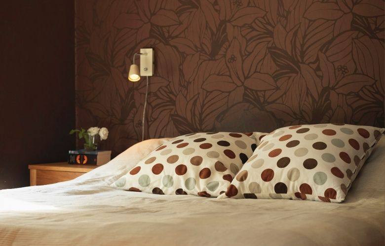 detalhe de cama branca com almofadas de bolinhas e papel de parede florido