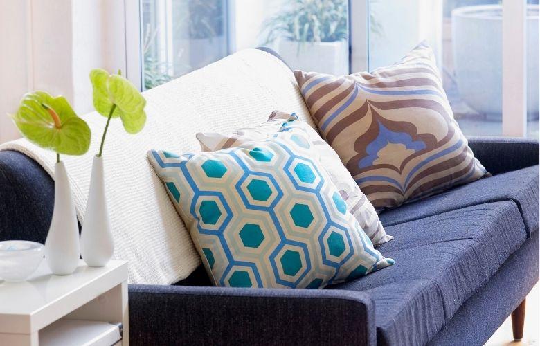 sofá azul em sala iluminada com almofadas estampadas