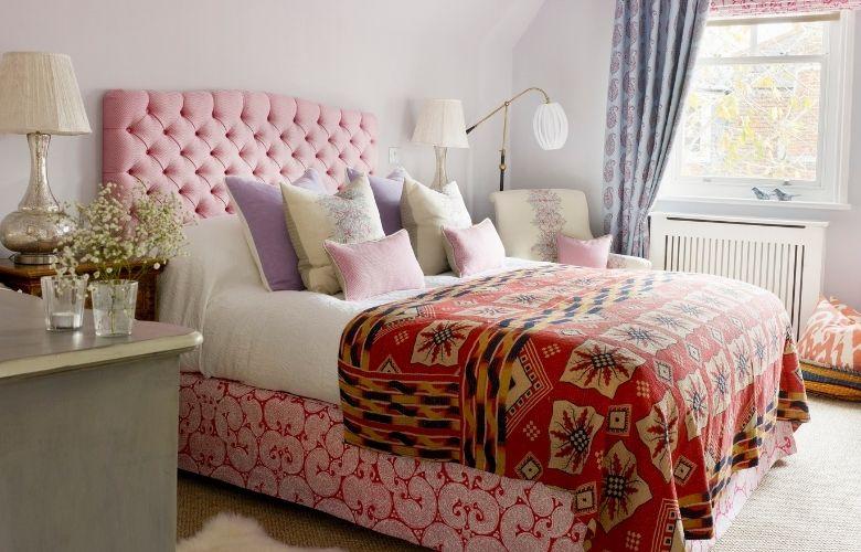 quarto em estilo boho com saia de cama rosa estampada e manta vermelha