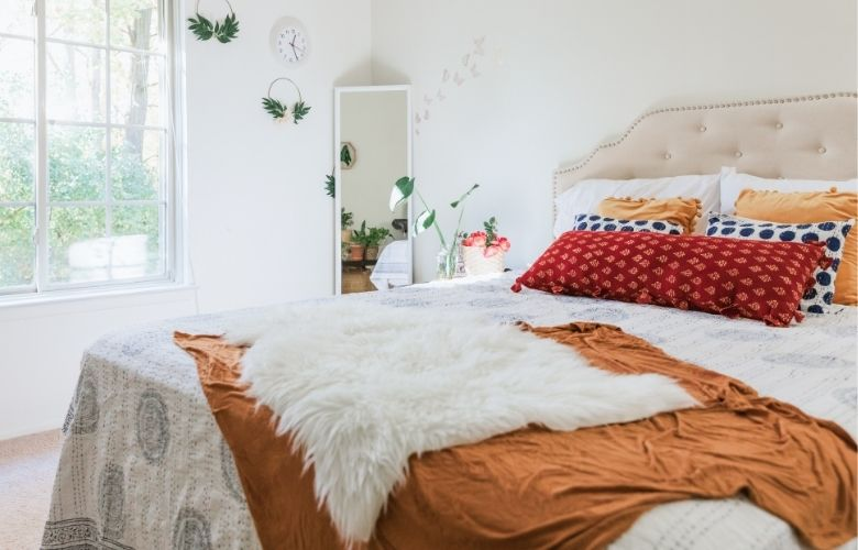 quarto branco com cama de manta laranja e almofadas coloridas