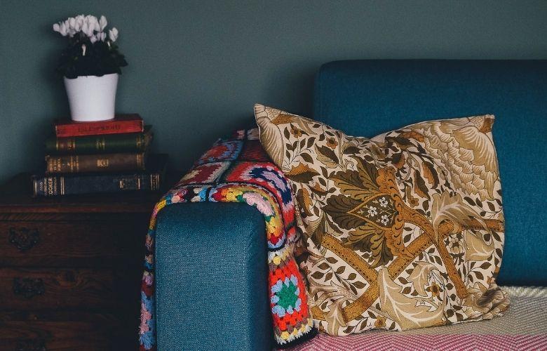detalhe de sofá azul com manta e almofada estampados de diferentes cores
