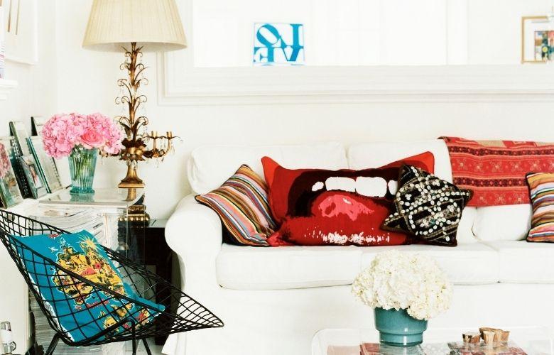 sala branca com cadeira em wireframe e sofa branco com almofadas coloridas e estampadas