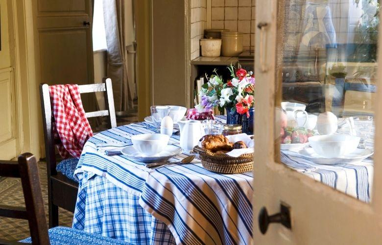 mesa posta em ambiente rustico com toalhas listradas e xadrez em tons de azul