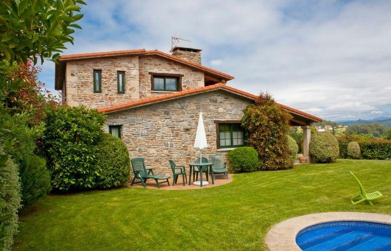 gramado amplo com piscina e casa de campo ao fundo em estilo rústico com revestimento em pedra