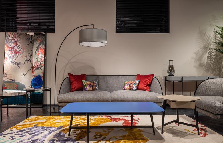 mistura de estampas tapetes e almofadas em sofá cinza-