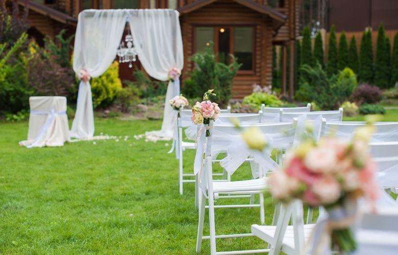 casamento no campo com altar e cadeiras decorados com pano branco e flores rosas casa de campo ao fundo