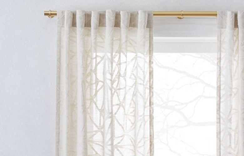 cortina bege neutra com trasços geométricose vaso de flo