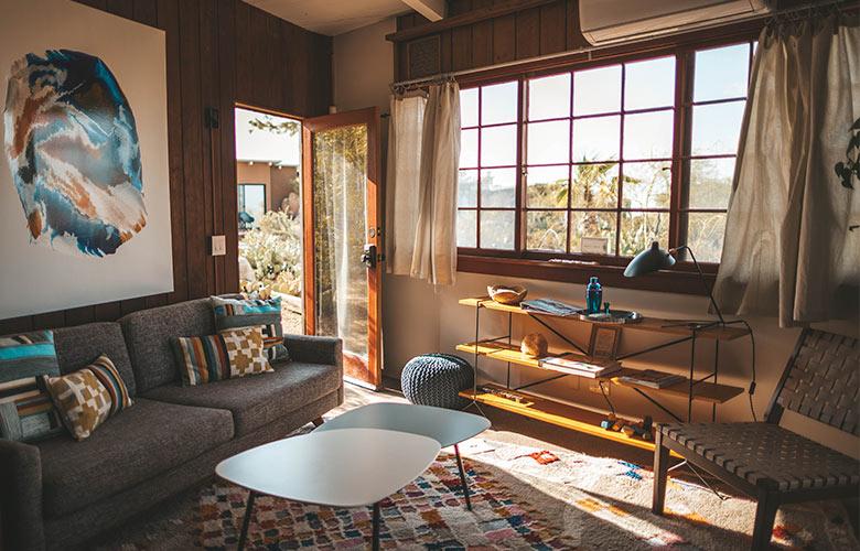 Casa de campo rústica e moderna com sofá chumbo, tapete, estante de madeira e ferro e mesas de centro retrô