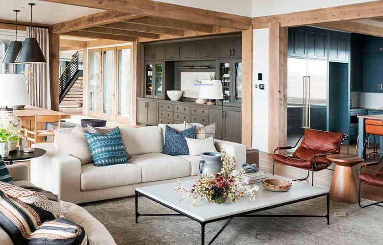 Decoração de casa de campo rústica, sala integrada com toda casa, estrutura de madeira, sofás brancos, poltrona de couro e armário cinza e azul