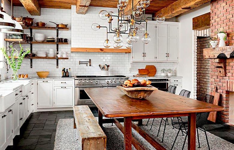 Cozinha e sala de jantar com mesa e armários rústicos, parede de tijolos à vista e azulejos metrô