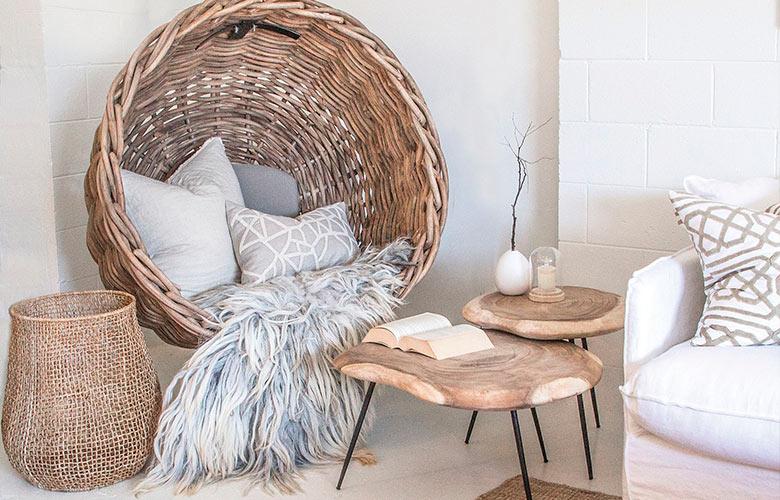 Decoração balanço de vime com manta de pelúcia e almofadas, mesas de centro de madeira de demolição, cesto de palha e tapete de sisal