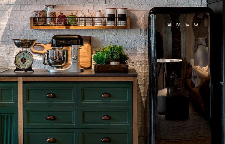 Cozinha casa de campo rústica, prateleiras de madeira, móvel de madeira com gavetas verde escuras, geladeira retrô preta, batedeira e balança