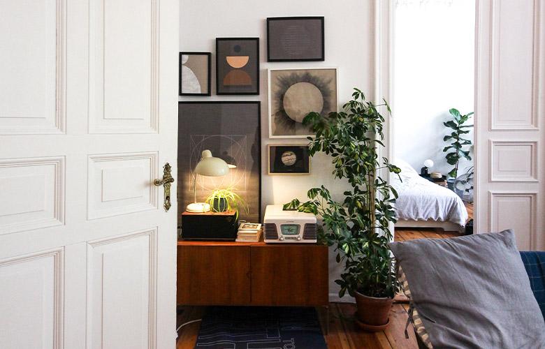 Decoração de sala de casa rústica com móveis e chão de madeira, mosaico de quadros, plantas, porta e parede brancas