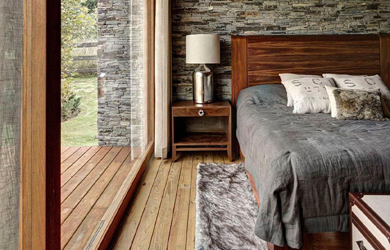 Quarto de casa de campo rústica com chão de madeira, tapete cinza pelúcia, parede de pedra e cama de casal de madeira