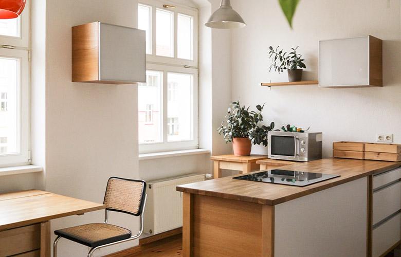 Decoração em cozinha de casa de campo rústica e moderna, móveis e bancada de madeira com cooktop e paredes brancas