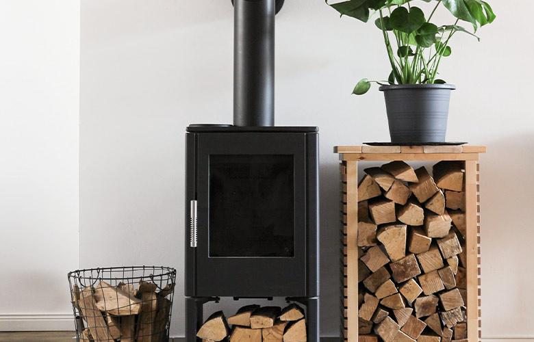Lareira em casa rústica de ferro preta e moderna, lenhas, parede branca e vaso com costela de adão