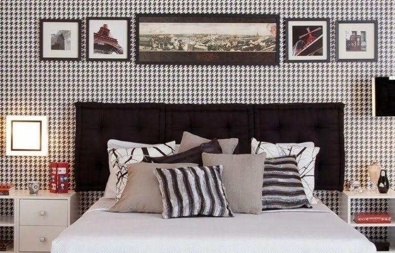 decoração para quarto com estamparia pied de poule em papel de parede e objetos, cama com cabeceira preta e almofadas, criado mudo branco com itens decorativos