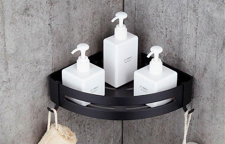 Banheiro com parede de cimento queimado e porta shampoo de canto de metal preto