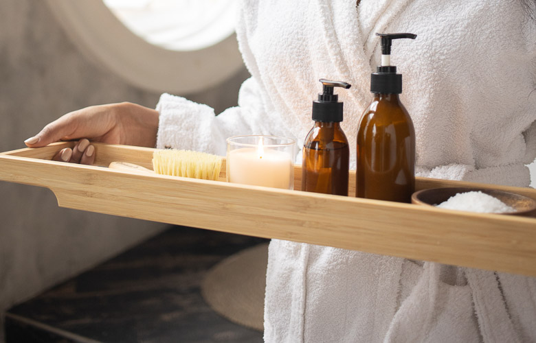 frascos de shampoo e óleos de vidro e saboneteira em bandeja de madeira-