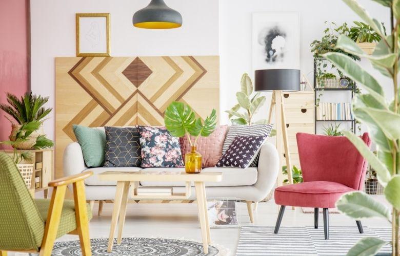 sala de estar colorida com painel geométrico em madeira atrás do sofá e almofadas de estampas geométricas e florais