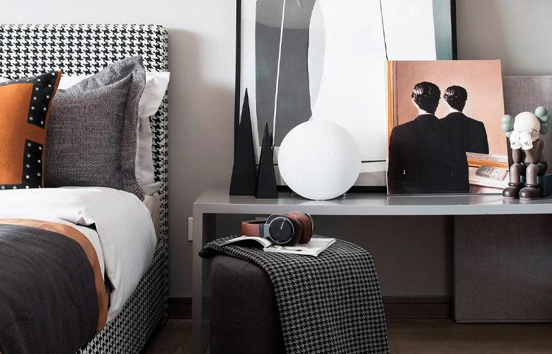 cama estofada com estampa pied de poule, banco como mesa lateral, quadros, luminária redonda e pufe preto