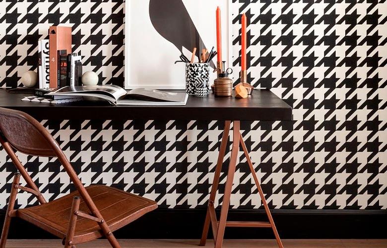 ATTACHMENT DETAILS escritório com papel de parede pied de poule, mesa tampo preto com cavalete marrom, cadeira de ferro, velas e quadro