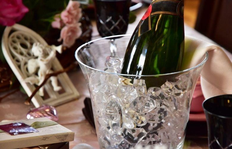 champanheira de acrílico com gelo e champanhe em mesa