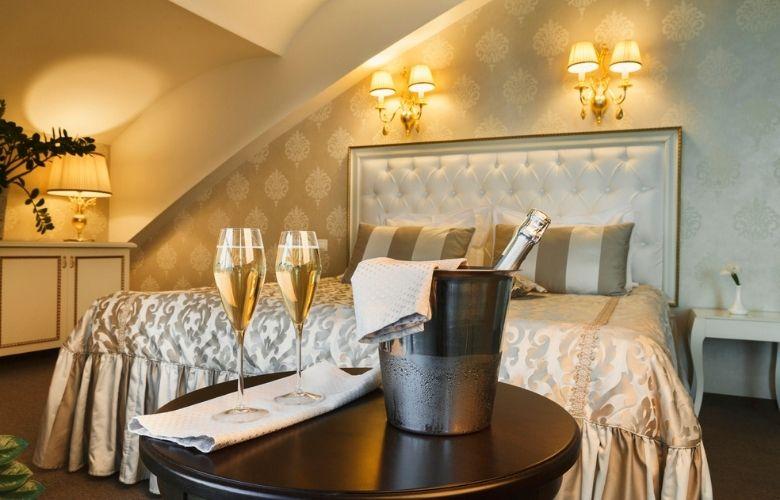 quarto amplo de casal com decoração bege, cama de casal clássica e mesa de apoio com champanheira