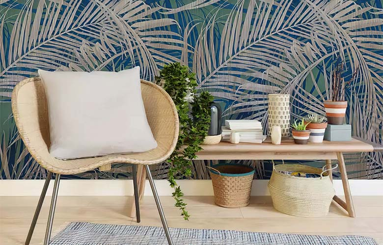 Parede decorada com estampa tropical cadeira com almofada branca mesa de canto de madeira com vasos de plantas
