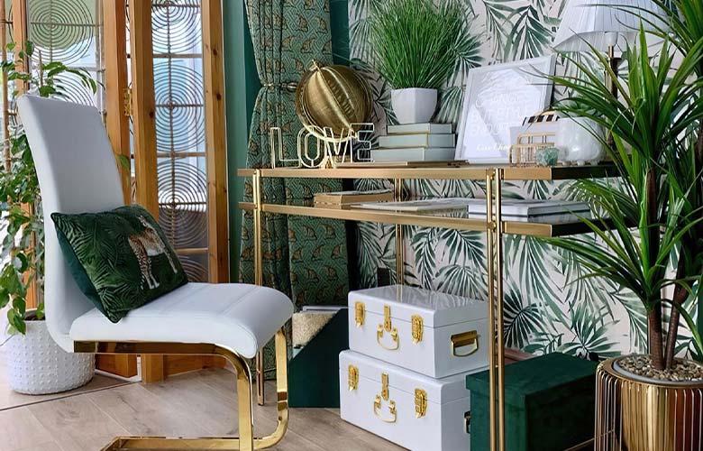 Parede decorada com estampa tropical com escrivaninha de madeira cadeira branca caixas piso de madeira e vaso de plantas