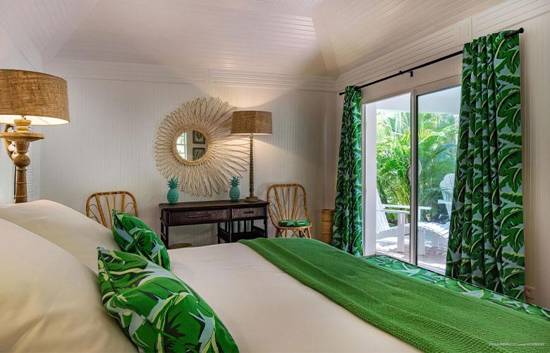 Quarto decorado em estilo tropical com cortinas e almofadas com estampa tropical verde cadeiras e luminárias