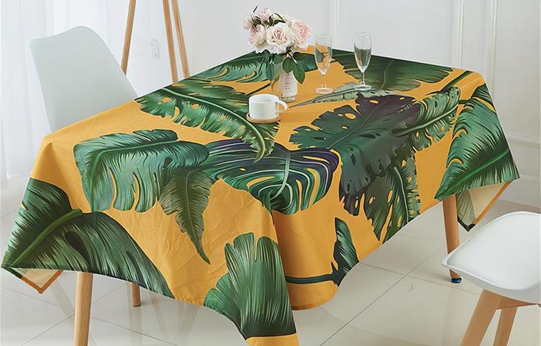 Mesa de madeira com toalha amarela de estampa tropical com folhas verdes