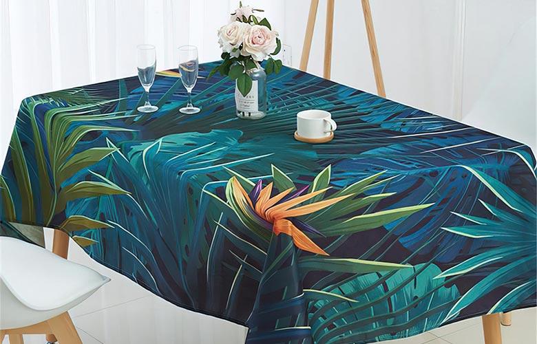 Mesa de madeira com toalha azul de estampa tropical com folhas verdes e azuis