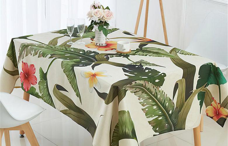 Mesa de madeira com toalha branca de estampa tropical com folhas verdes e flores