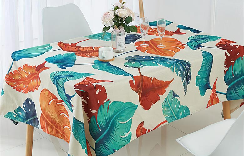 Mesa de madeira com toalha branca de estampa tropical com folhas verdes vermelhas e laranjas