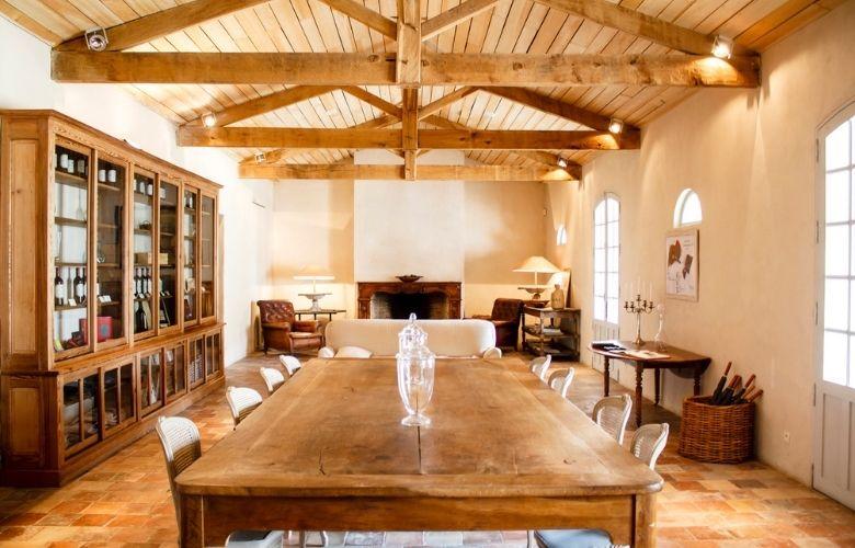 Sala de jantar com móveis country como mesa de madeira, armário grande de madeira e portas com vidro