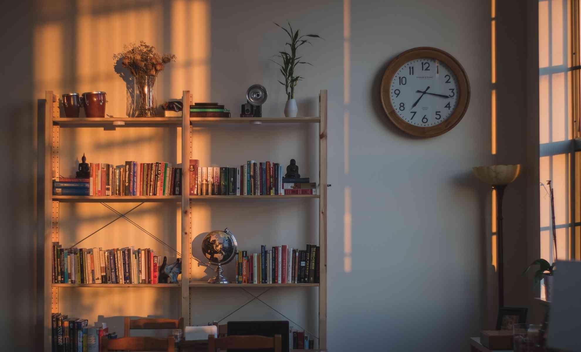 decoração com livros em estilo natural em estante de madeira, relógio de parede