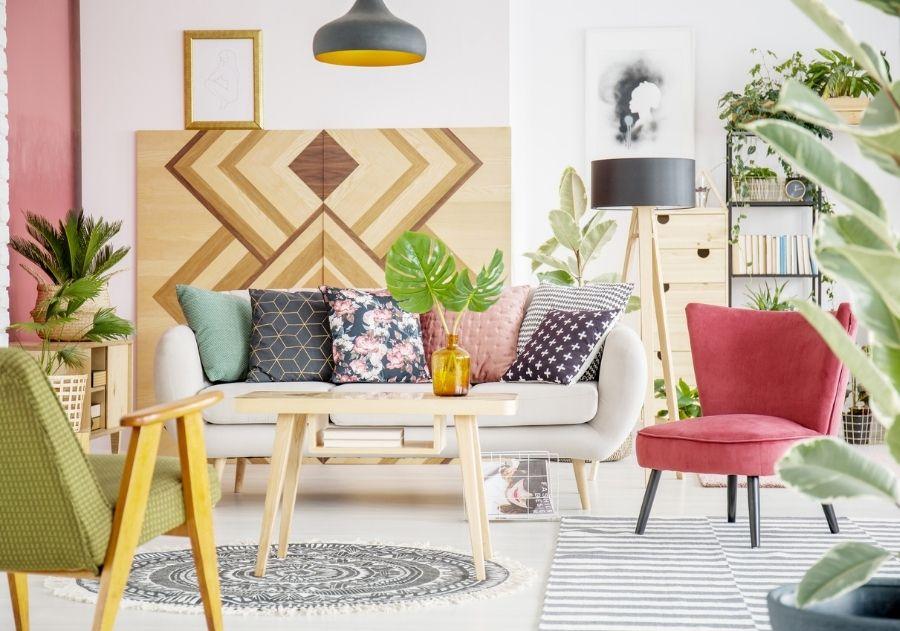 decoração com almofadas estampadas, florais e lisas no sofá branco na sala colorida com plantas