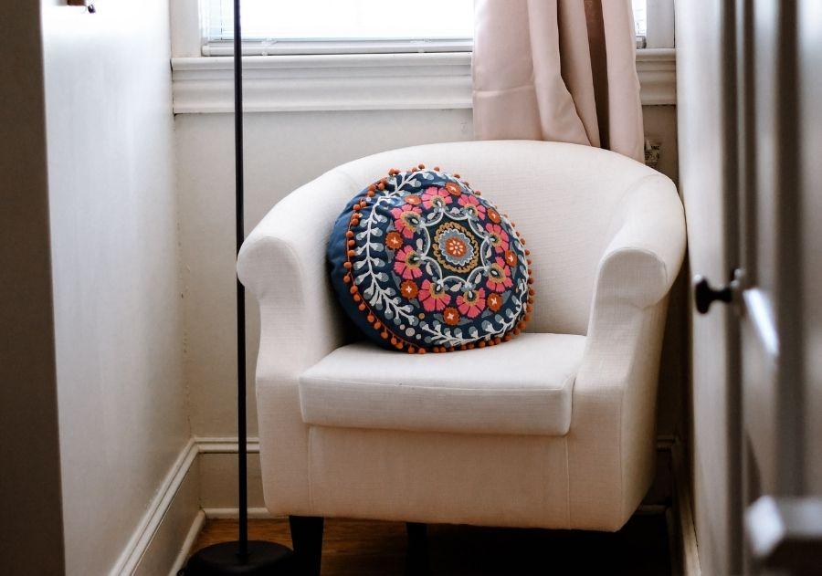 poltrona clássica branca com almofada estampada colorida