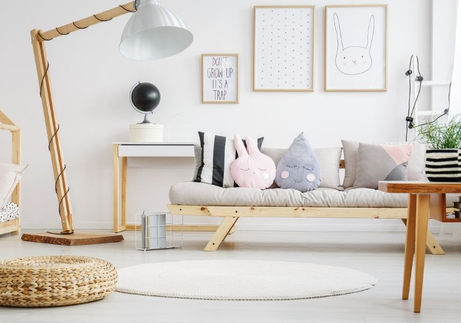 decoração com almofadas em tamanhos e modernos diferentes sobre sofá cinza de madeira com tapete em tons claros
