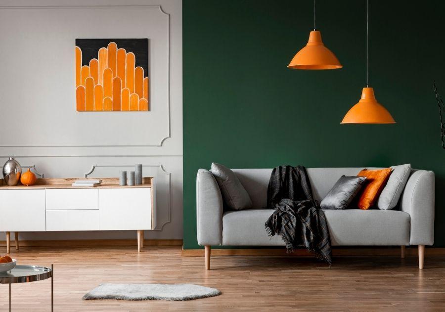 sofá cinza decorado com almofadas cinzas e laranjas com manta preta