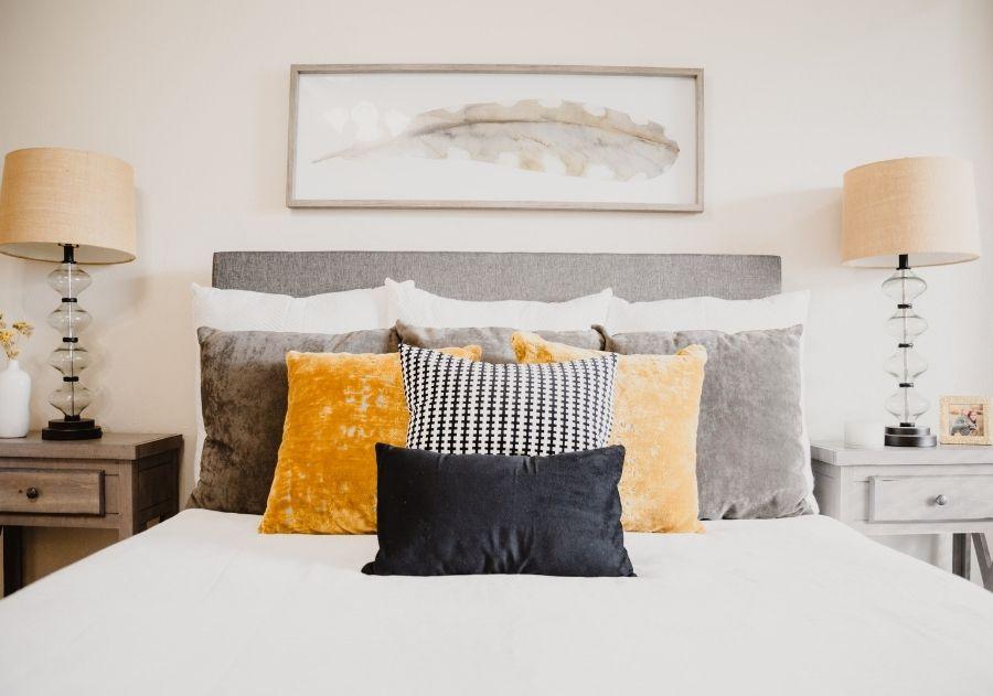 almofadas na cama em diferentes tamanhos e cores
