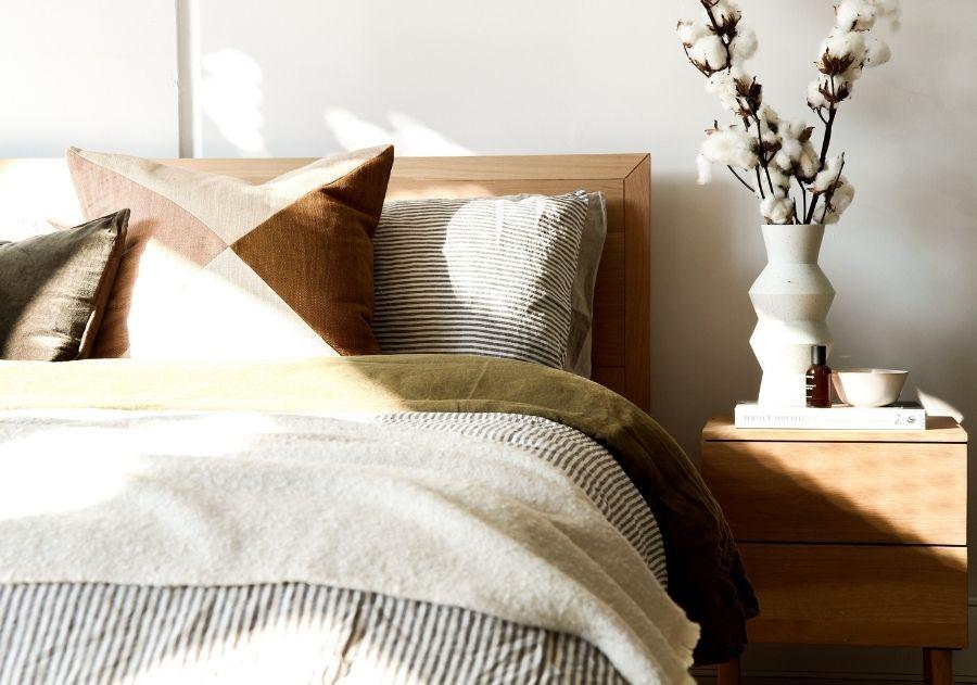 cama de casal decorada com almofadas em tons terrosos